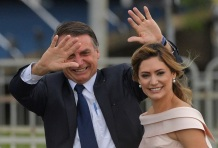 Brazil's President-elect Jair Bolsonaro (L) gestures next to his wife Michelle Bolsonaro as the presidential convoy heads to the National Congress for his swearing-in ceremony, in Brasilia on January 1, 2019. - Bolsonaro takes office with promises to radically change the path taken by Latin America's biggest country by trashing decades of centre-left policies. (Photo by Carl DE SOUZA / AFP)